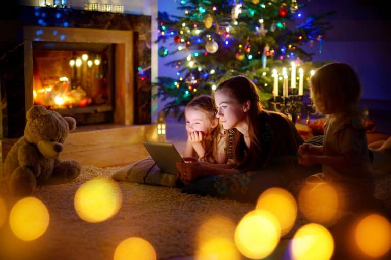 Familie in weihnachtlichem Wohnzimmer mit Tablet