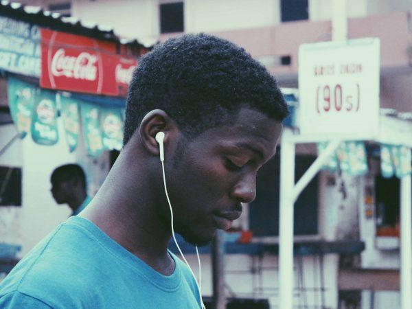 Junger Mann mit In-Ear Kopfhörer hört Musik