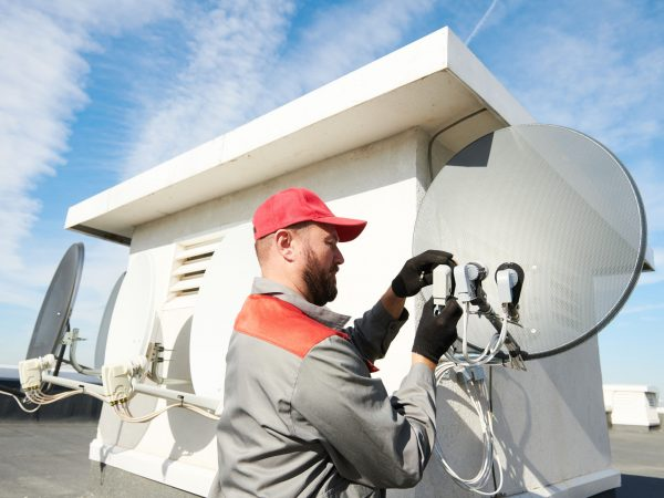 Service man worker installing and fitting satellite antenna dish for cable TV or broadcast