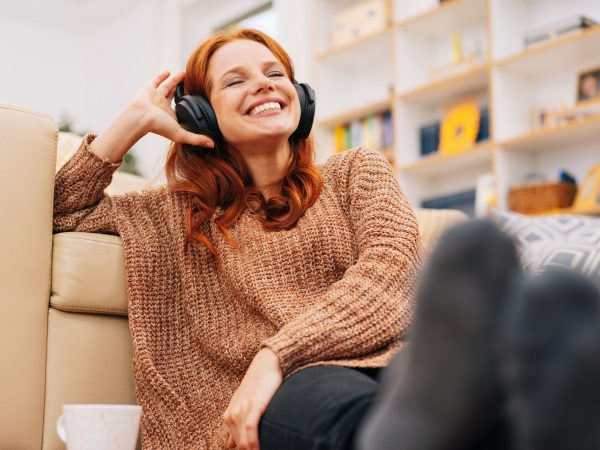 Happy woman relaxing at home with headphones listening to music