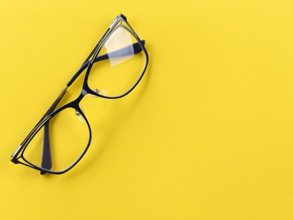 transparent glasses for vision with black arms on a bright yellow background, with glare on the glass. place for text